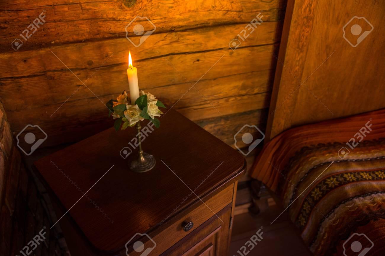 Lit Kerze In Kerzenständer Mit Weißen Rose Dekorationen, Blumen Und Grünen  Blättern Auf Rustikalen Nachttisch
