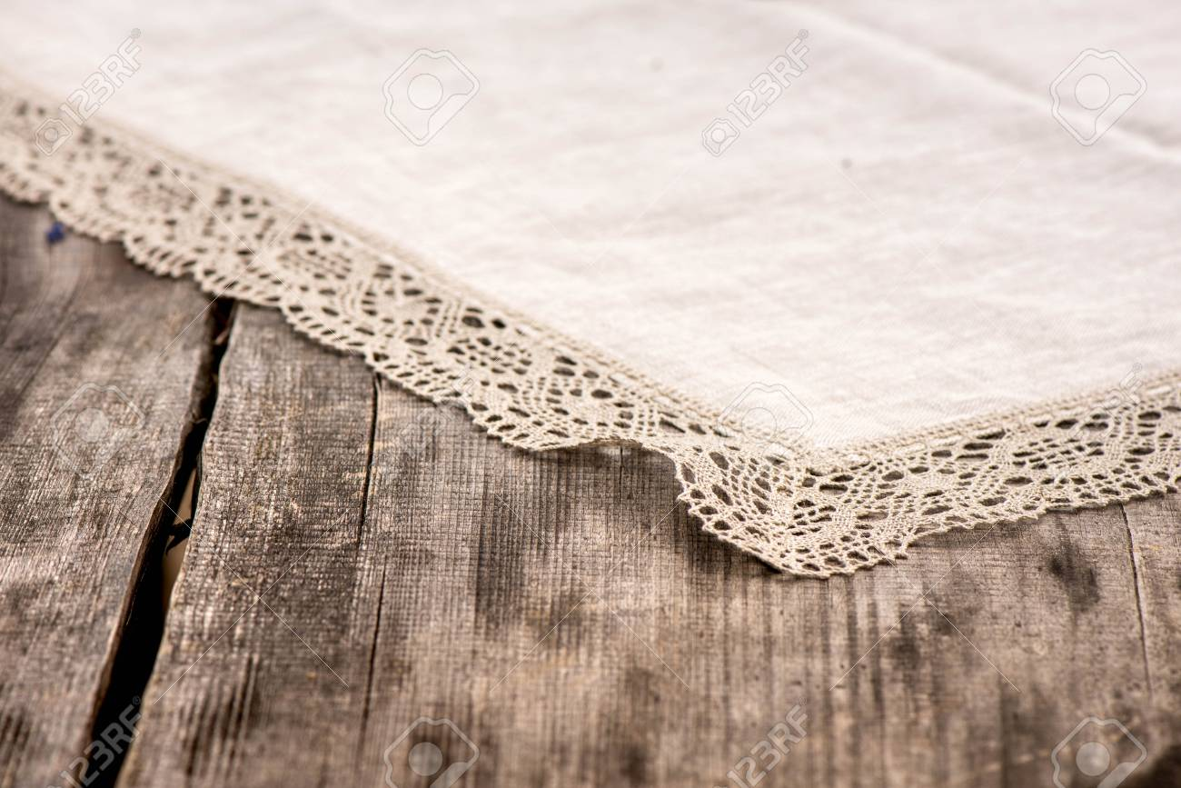Shot Of Linen Tablecloth With Grey Crochet Lace Trim On A Wooden