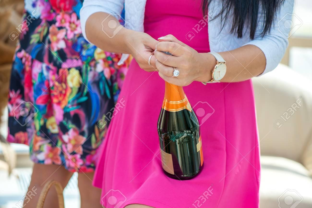 La Muchacha En Vestido Rosado Está Abriendo La Botella De Champán ...