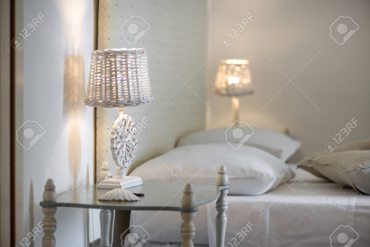 Lit up white bedroom lamps with beautiful ornaments standing..