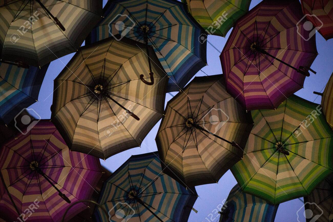 Night shot of colorful umbrellas in small street in middle of city on blue evening sky background. Romantic walk in rainy day - 119718500