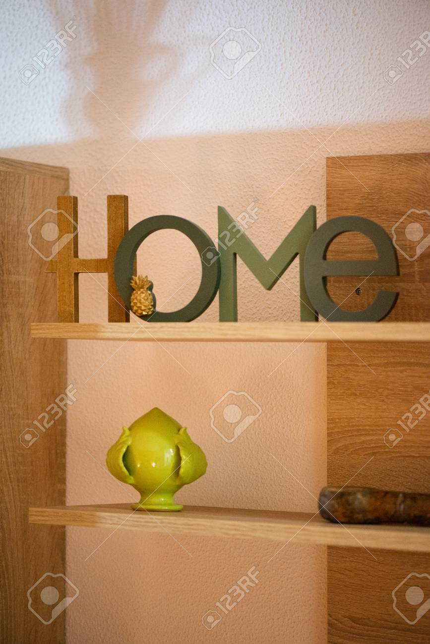 Home is where the heart is. Decorative sign standing in shelf next to old looking vintage books with ornaments. Cozy atmosphere in home or apartment. - 119718680