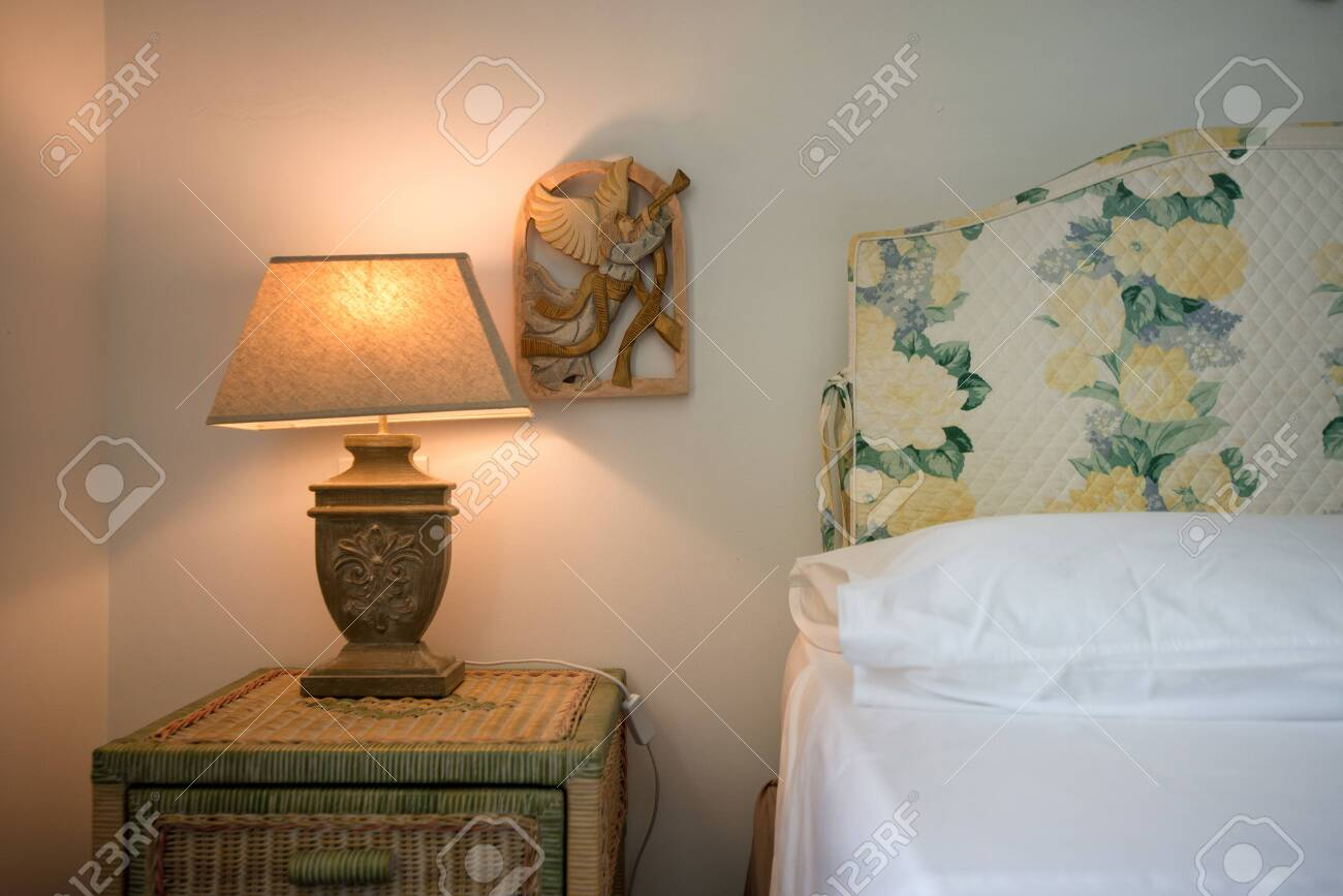 Lit up white bedroom lamps standing on wooden tables. Neutral colored modern bedroom with stylish interior design elements to set a warm and homely mood and atmosphere. Decorative flower ornaments - 119718682