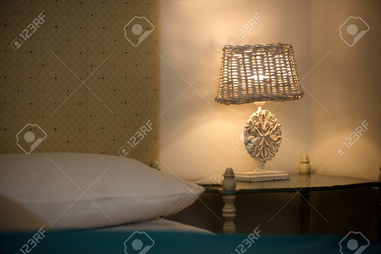 Bright eco light in the corner of a modern bedroom. New led technology meets traditional interior design. Lamp is creating cozy atmosphere in room. Wooden, glass table, blue curtains - 119718709