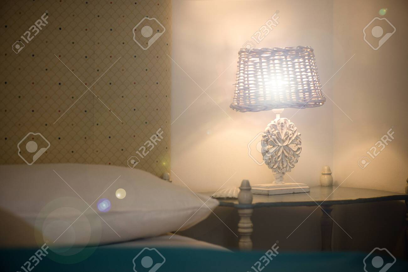 Bright eco light in the corner of a modern bedroom. New led technology meets traditional interior design. Lamp is creating cozy atmosphere in room. Wooden, glass table, blue curtains - 119718710