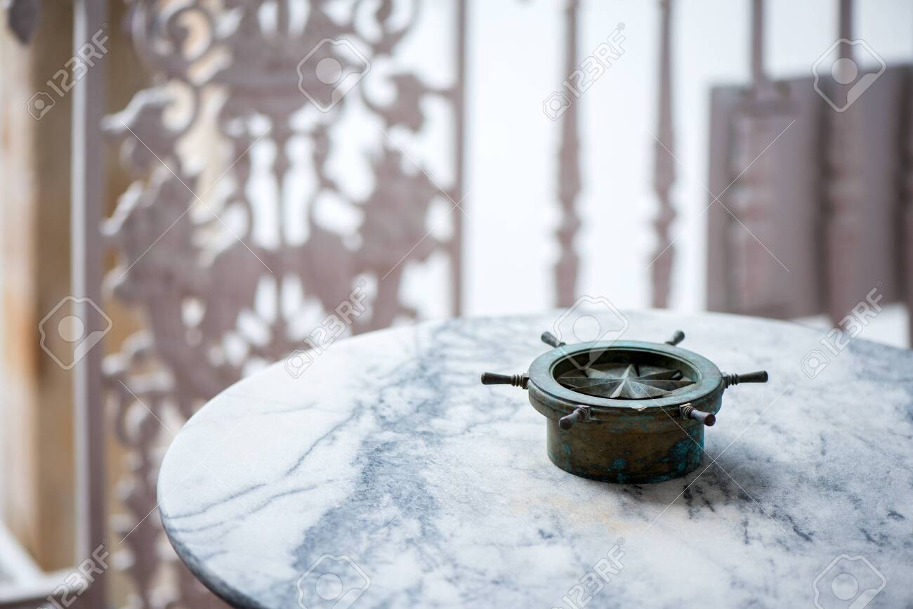 Vintage, old, rustic and ancient compass or steering wheel standing on table on balcony as a decoration. Beautiful, calm, sunny morning on yacht or ship. Concept of traveling - 119718711