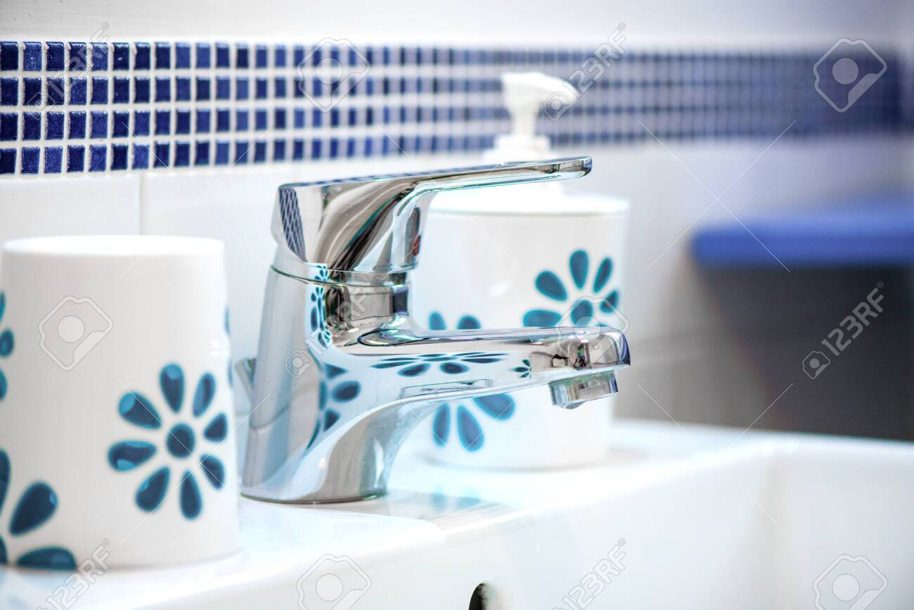 Modern tiled bathroom sink basin faucet paired with clay soap containers. Concept of cleaning the bathroom. - 119718713