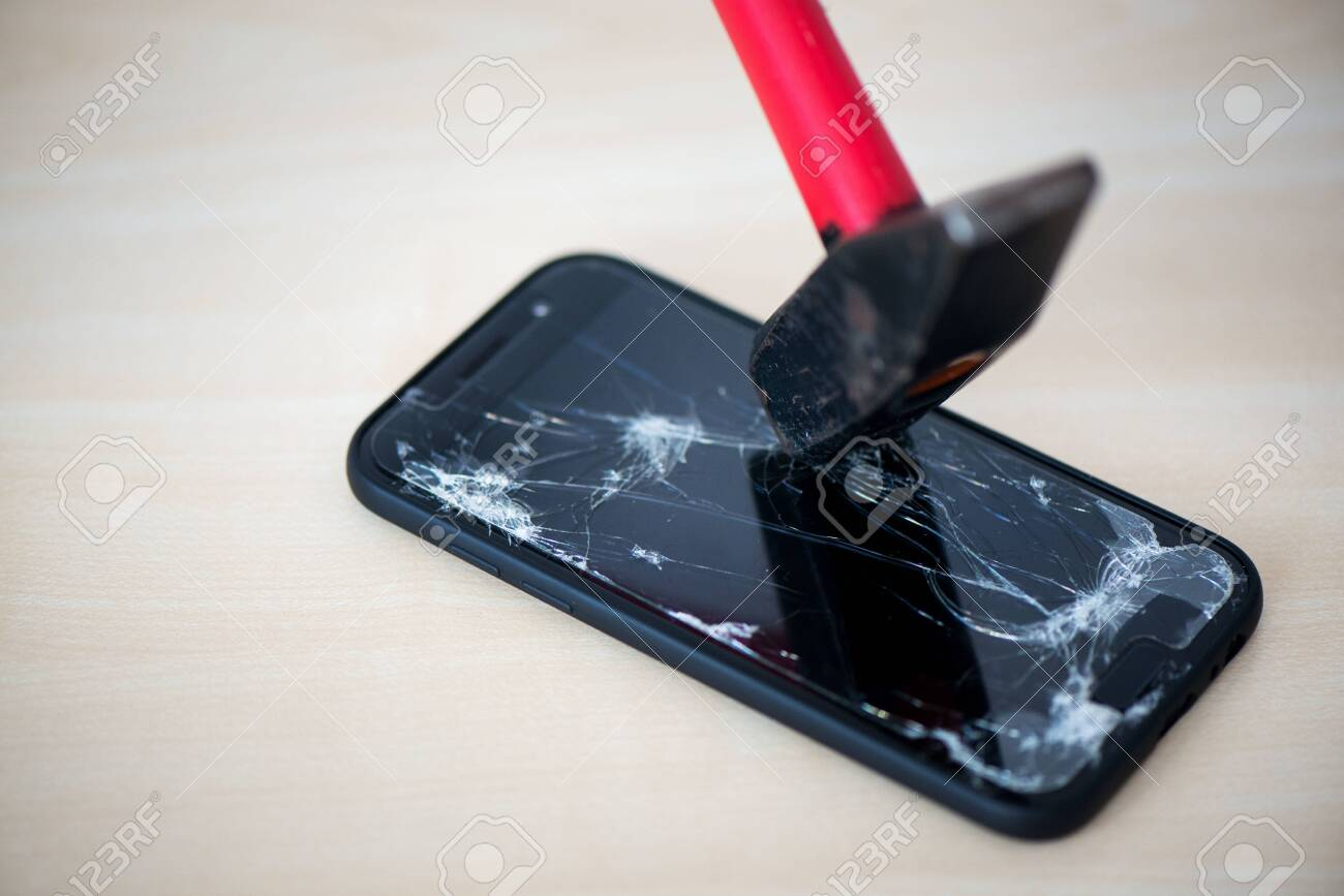 Hammer cracking on smartphone. Screen and display is destroyed, damaged and cracked. Concept of anger, rage and repairing electronic devices. Valid warranty - 119718842