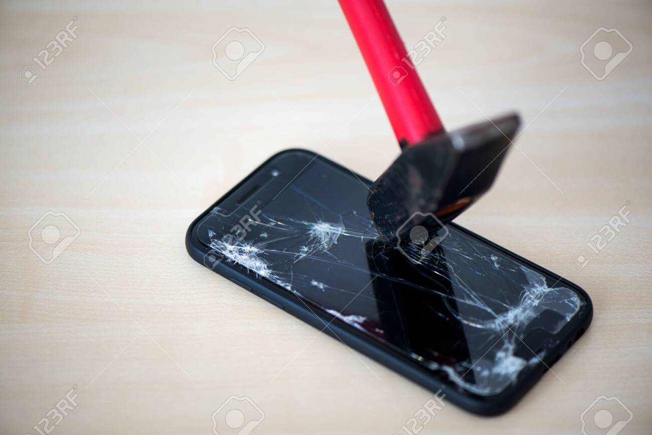 Hammer cracking on smartphone. Screen and display is destroyed, damaged and cracked. Concept of anger, rage and repairing electronic devices. Valid warranty - 119718892