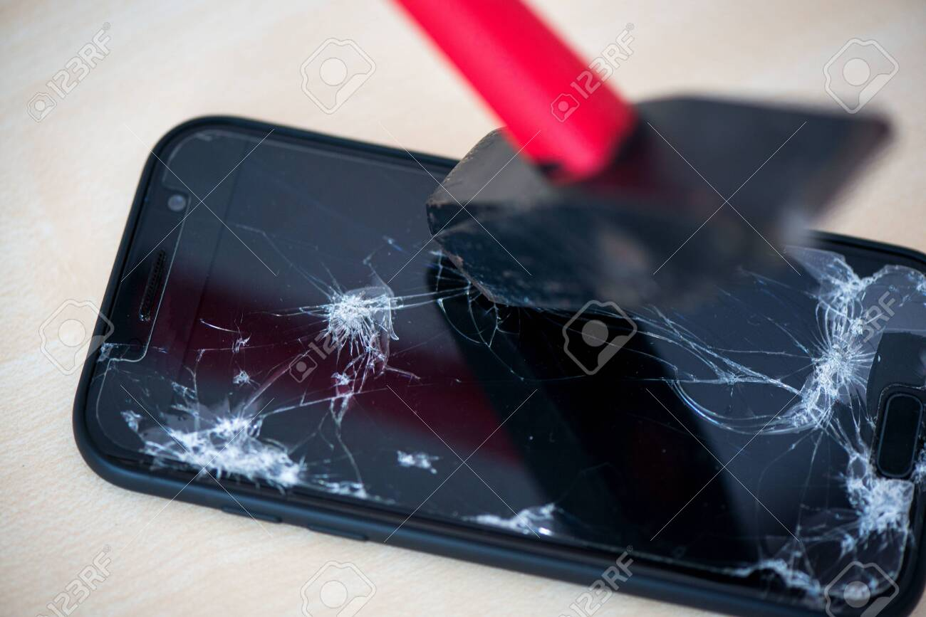 Hammer cracking on smartphone. Screen and display is destroyed, damaged and cracked. Concept of anger, rage and repairing electronic devices. Valid warranty - 119718894