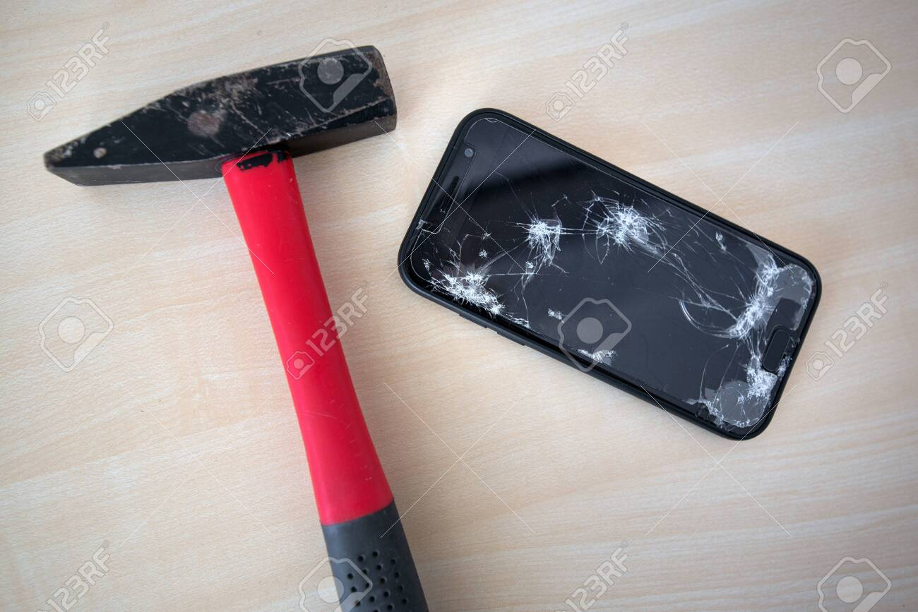 Hammer cracking on smartphone. Screen and display is destroyed, damaged and cracked. Concept of anger, rage and repairing electronic devices. Valid warranty - 119718898