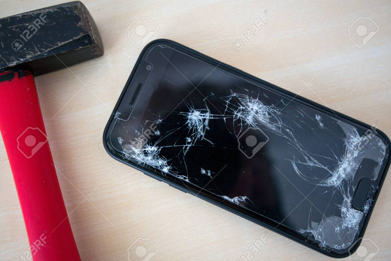 Hammer cracking on smartphone. Screen and display is destroyed, damaged and cracked. Concept of anger, rage and repairing electronic devices. Valid warranty - 119718899