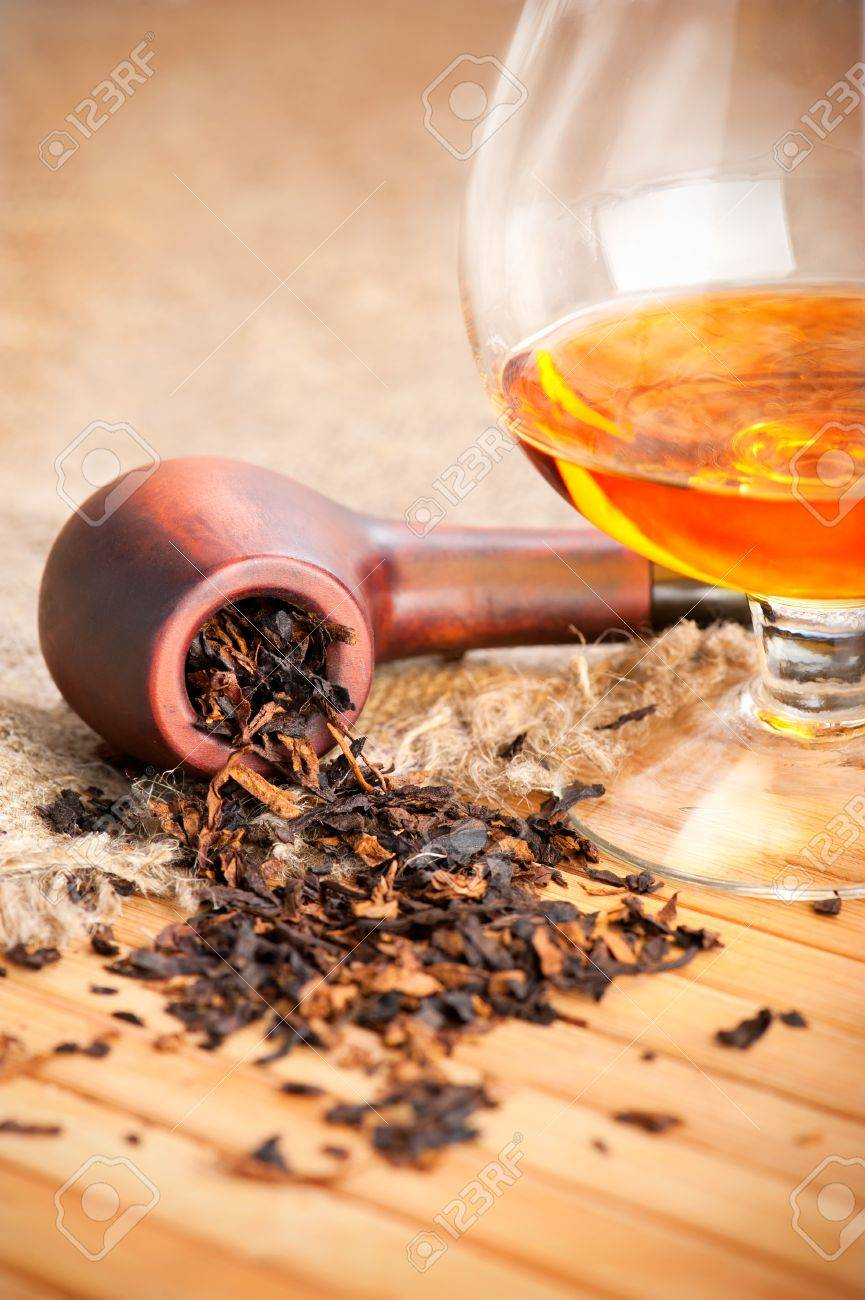 Glass of cognac and pipe with tobacco on wooden table with linen canvas Stock Photo - 11598937