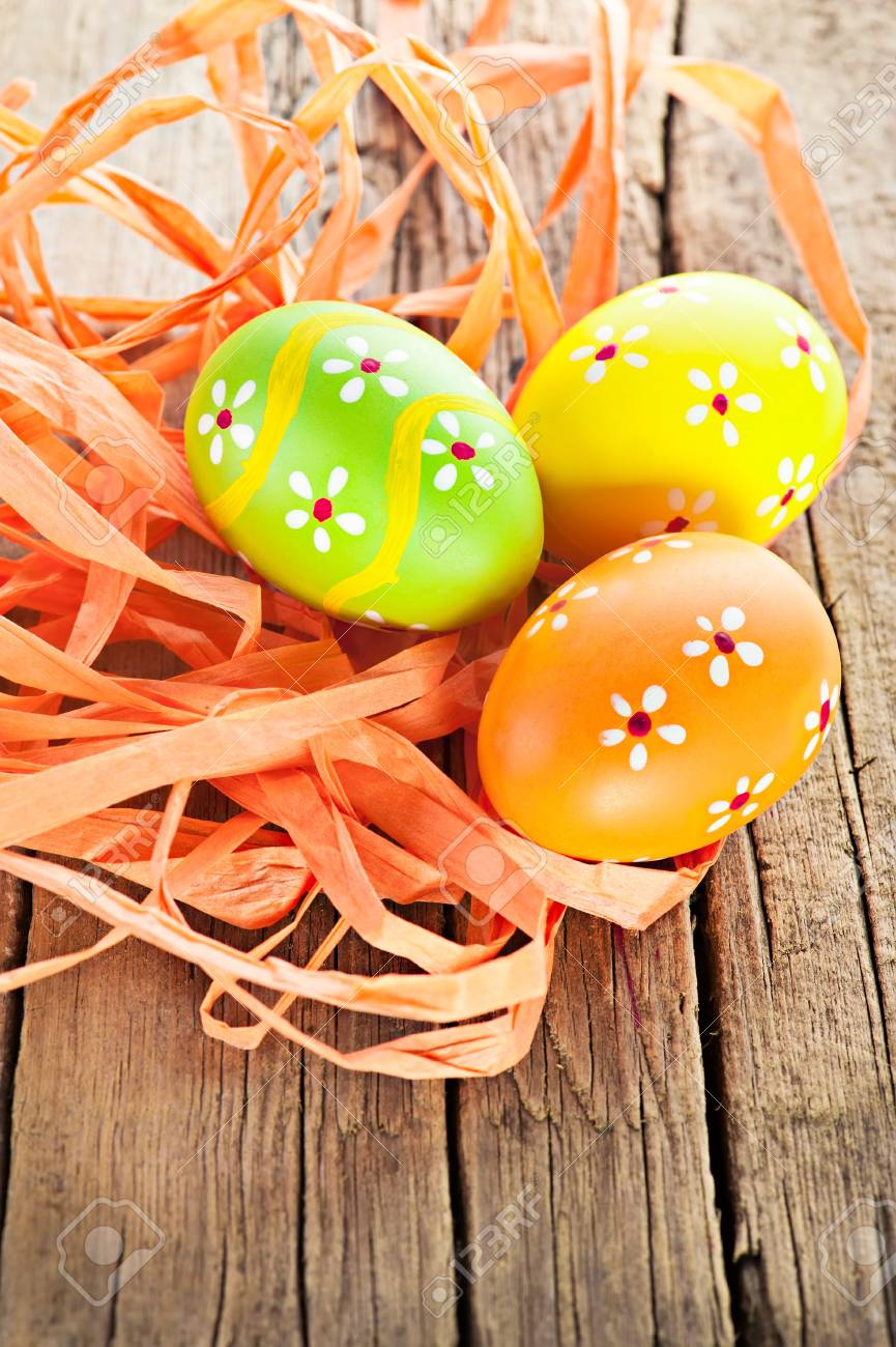 Easter background. Macro shot of painted eggs and ribbon decoration on old wooden texture Stock Photo - 12809488