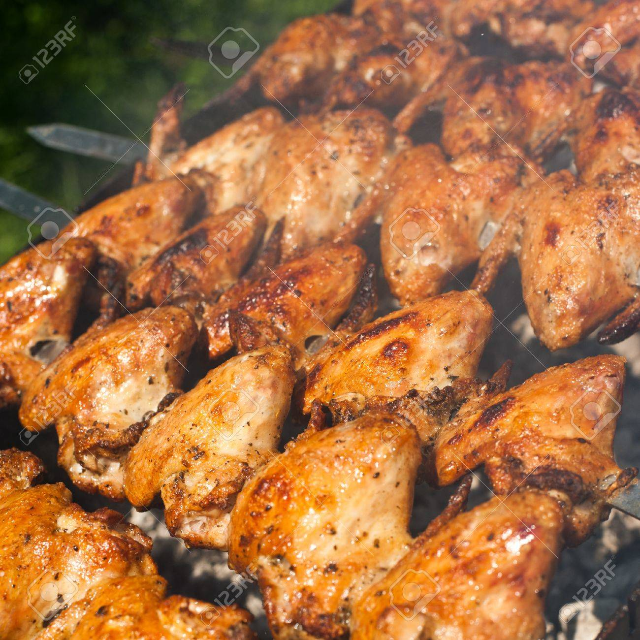 Cooking delicious juicy chicken wings at outdoors grill Stock Photo - 20954734