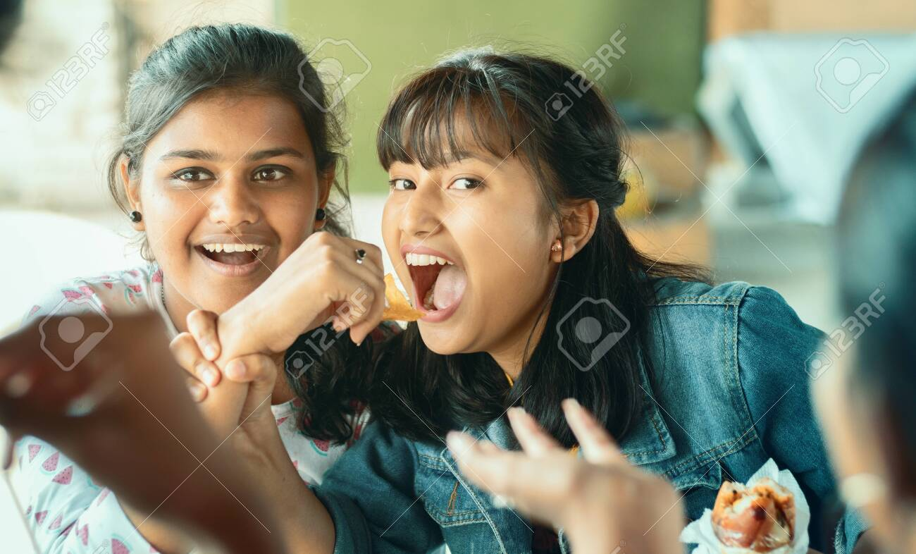 Teenager trying to take or grab food from friend - young girl playfully fighting for snacks with her friend - concept of friends having fun while having food at college restaurant. - 141784227
