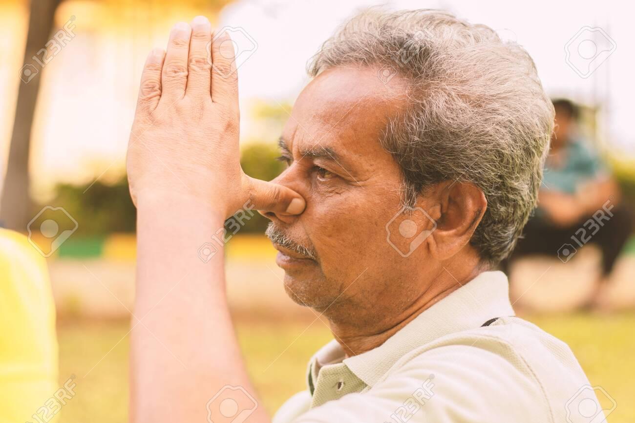 Closeup of of senior man doing alternate Nostril Breathing exercise or nadi shodhana pranayama at park - Concept of healthy active old people lifestyle. - 152416127