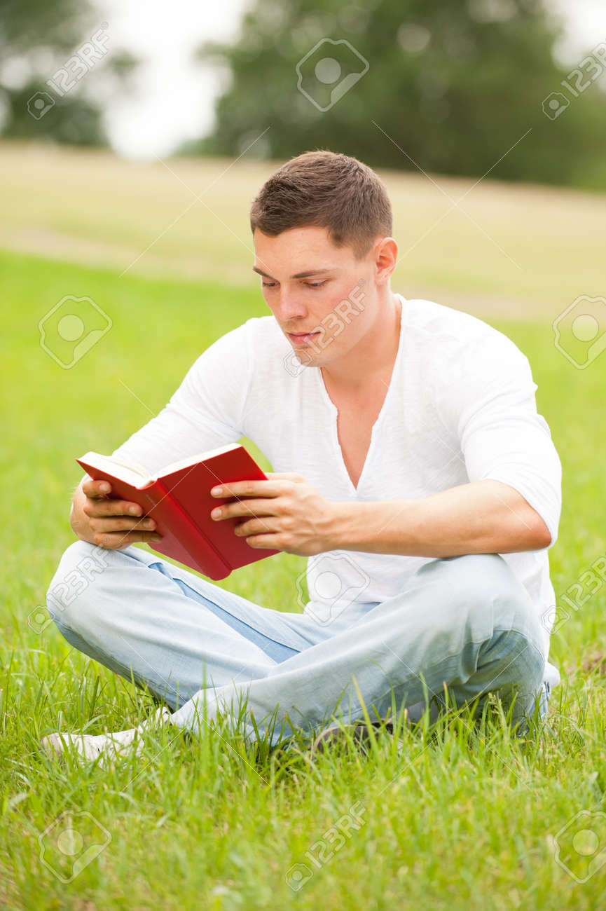 Young man with book in the park Stock Photo - 12450731