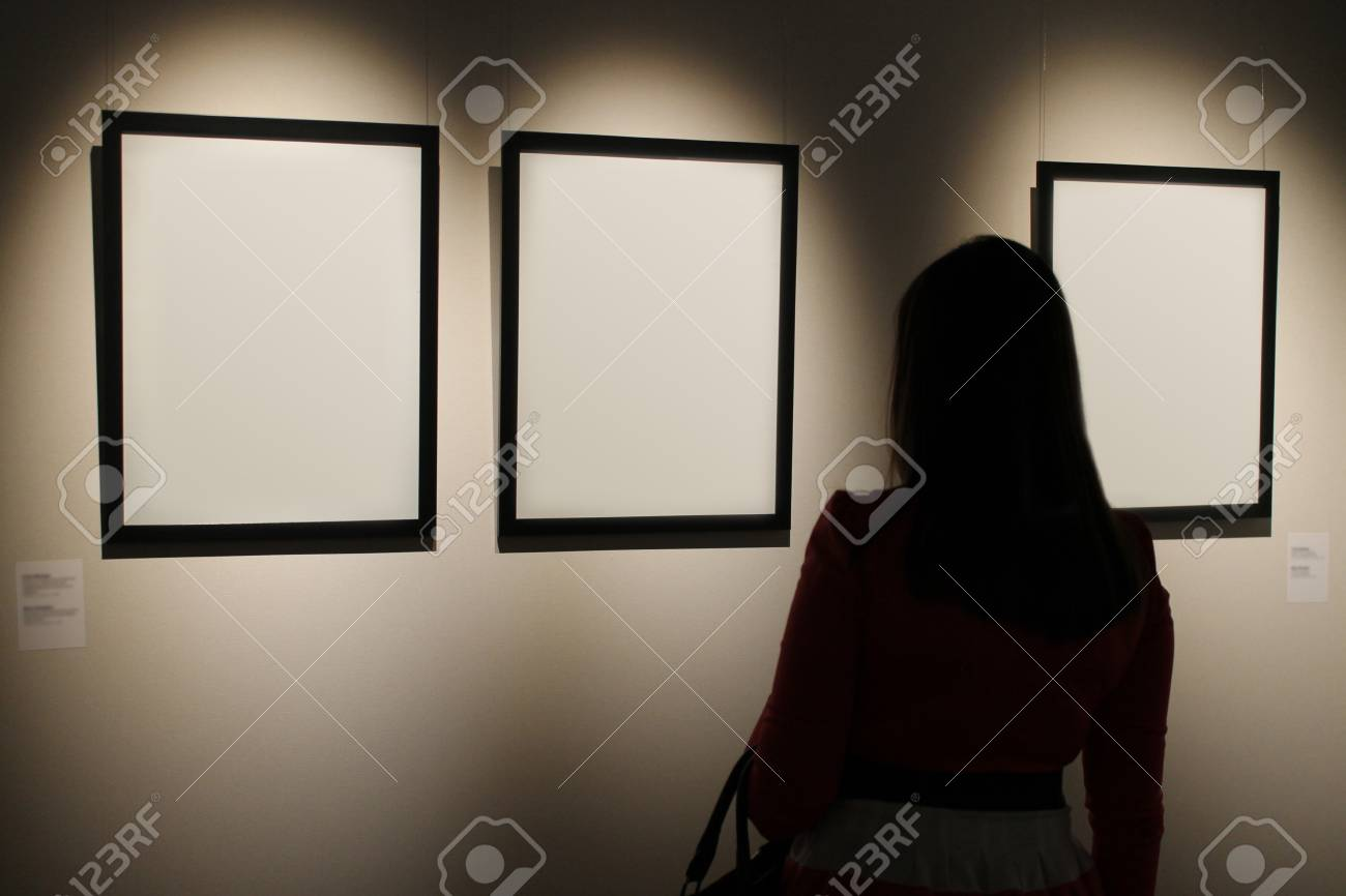 Three Blank White Canvas Frames Hang On Wall With Light Shining