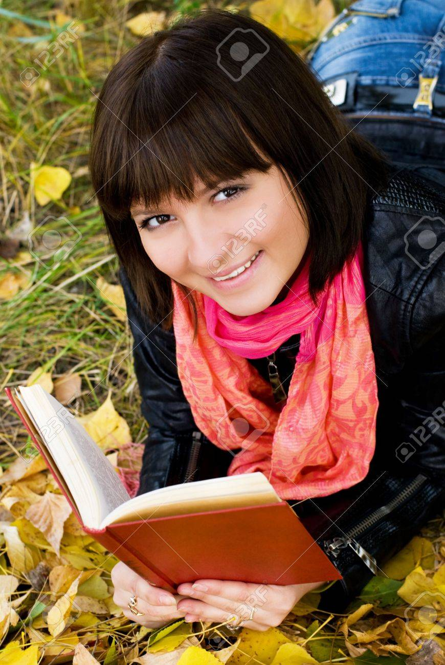 beautiful smiling girl with a book in the park Stock Photo - 3780720