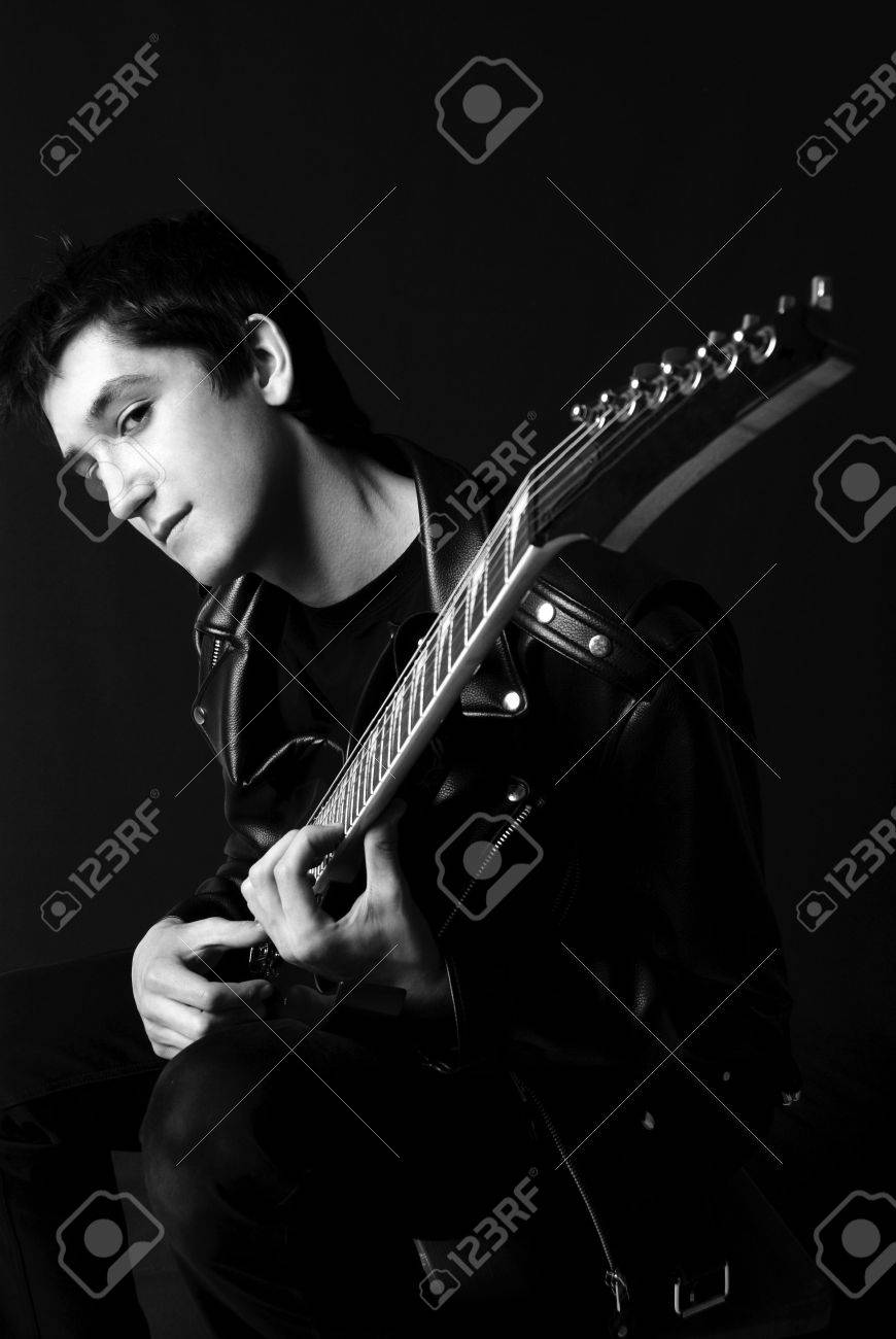 black and white portrait of a handsome young man sitting on the chair and playing guitar Stock Photo - 4519962