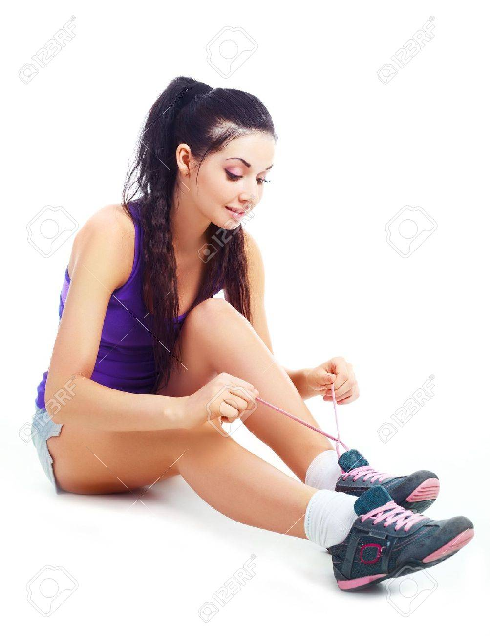 pretty brunette girl wearing sports clothes tying shoelaces Stock Photo - 8191328
