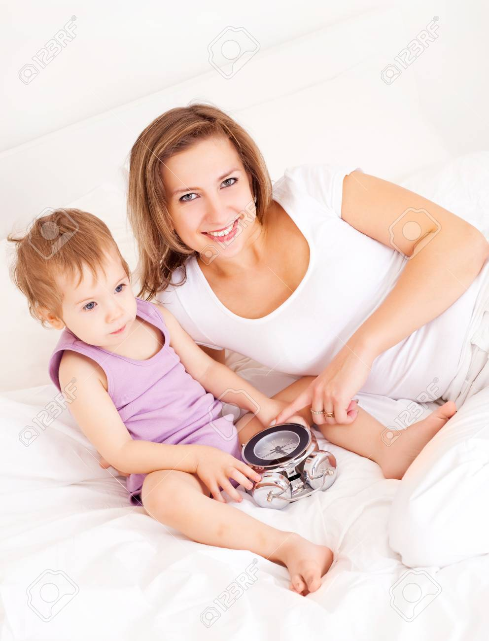 young beautiful mother and her baby on the bed at home Stock Photo - 8402438