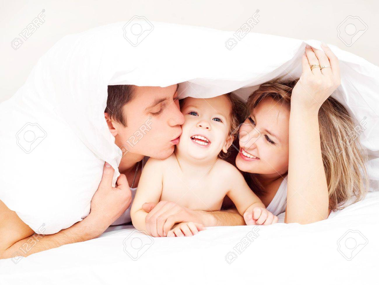 happy family, mother ,father and their baby under the blanket on the bed at home (focus on the man) Stock Photo - 8402429