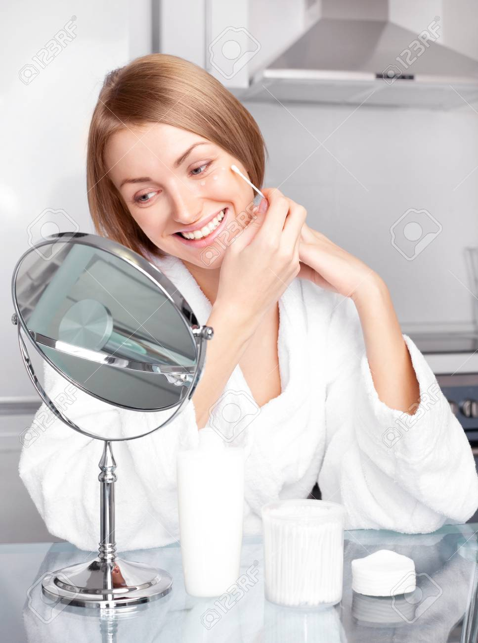beautiful young woman applying cream on her face at home Stock Photo - 8677682