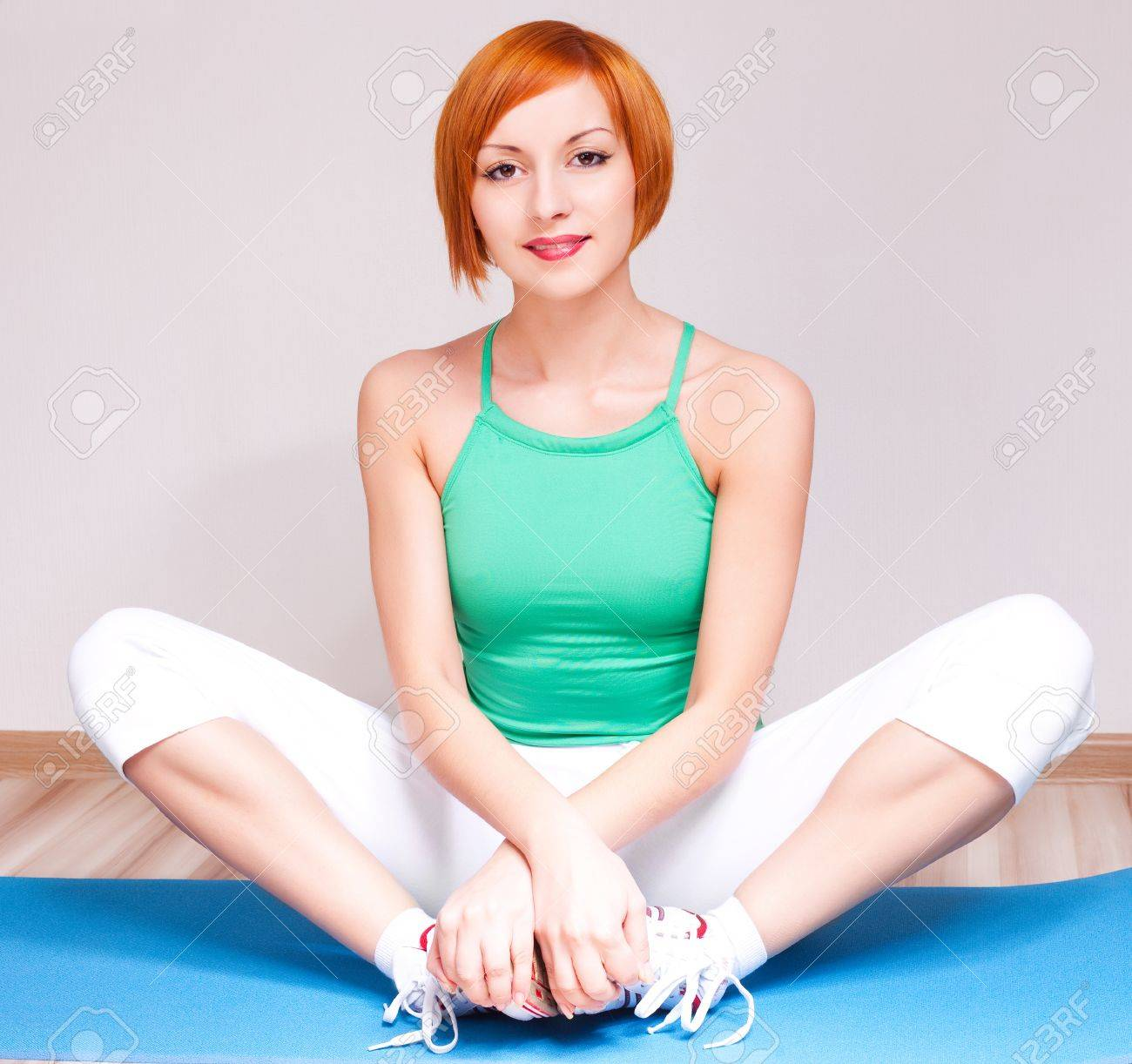 beautiful young sporty woman stretching the muscles of her legs on the mat at home Stock Photo - 9078104
