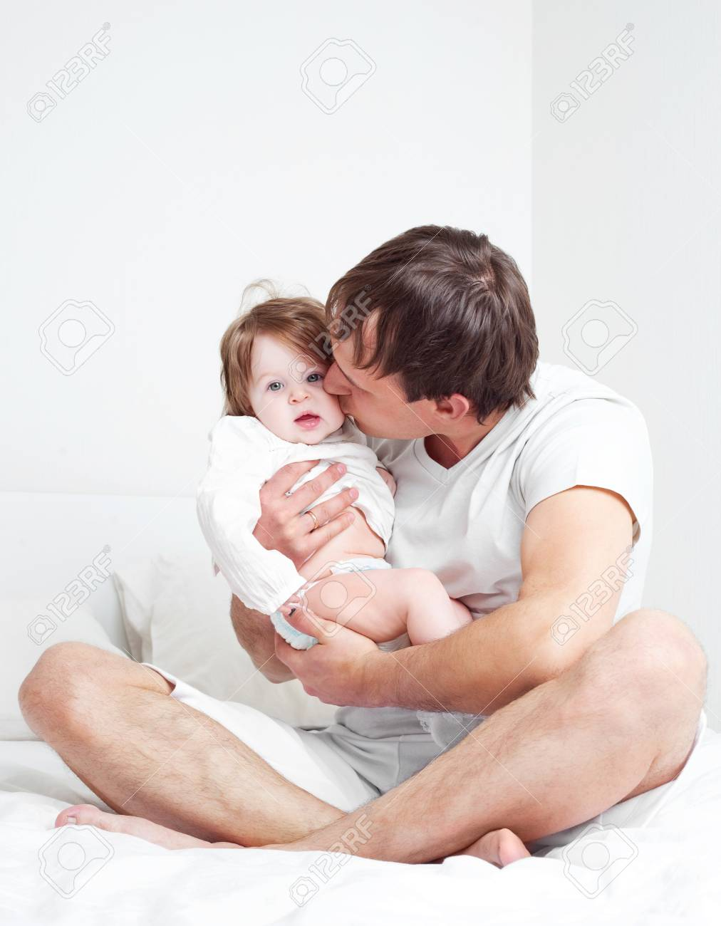 young father with his six months old daughter on the bed at home Stock Photo - 9155447