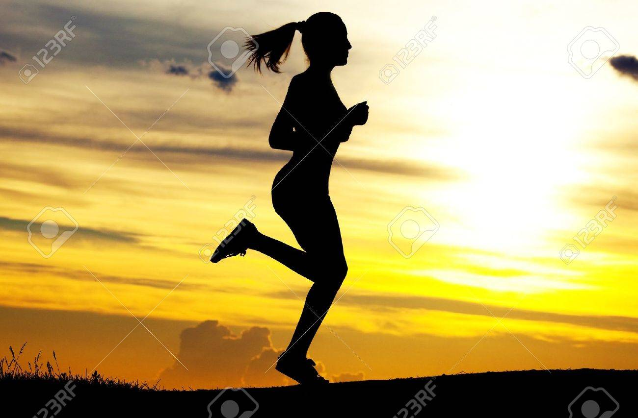 Silhouette of a beautiful running woman against yellow sky with clouds at sunset Stock Photo - 9759643