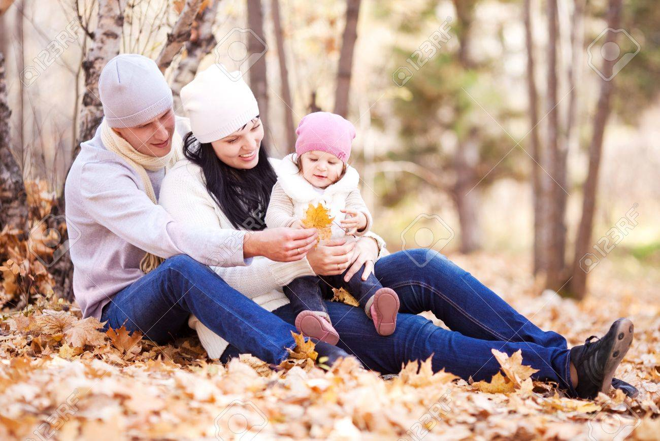 happy young family with their daughter spending time outdoor in the autumn park (focus on the woman) Stock Photo - 10794760