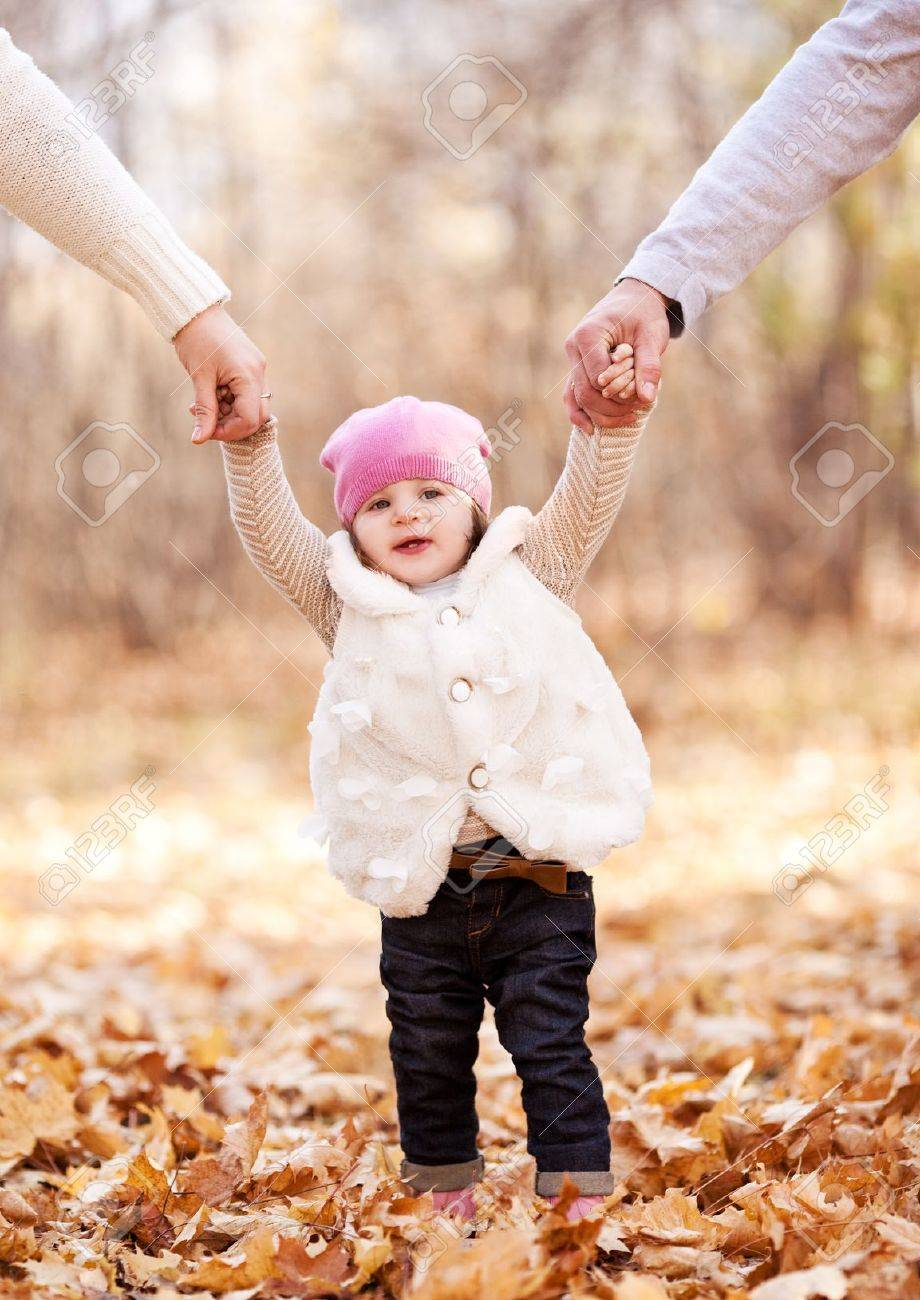 happy family with their baby spending time outdoor in the autumn park  and teaching her walking Stock Photo - 10794769