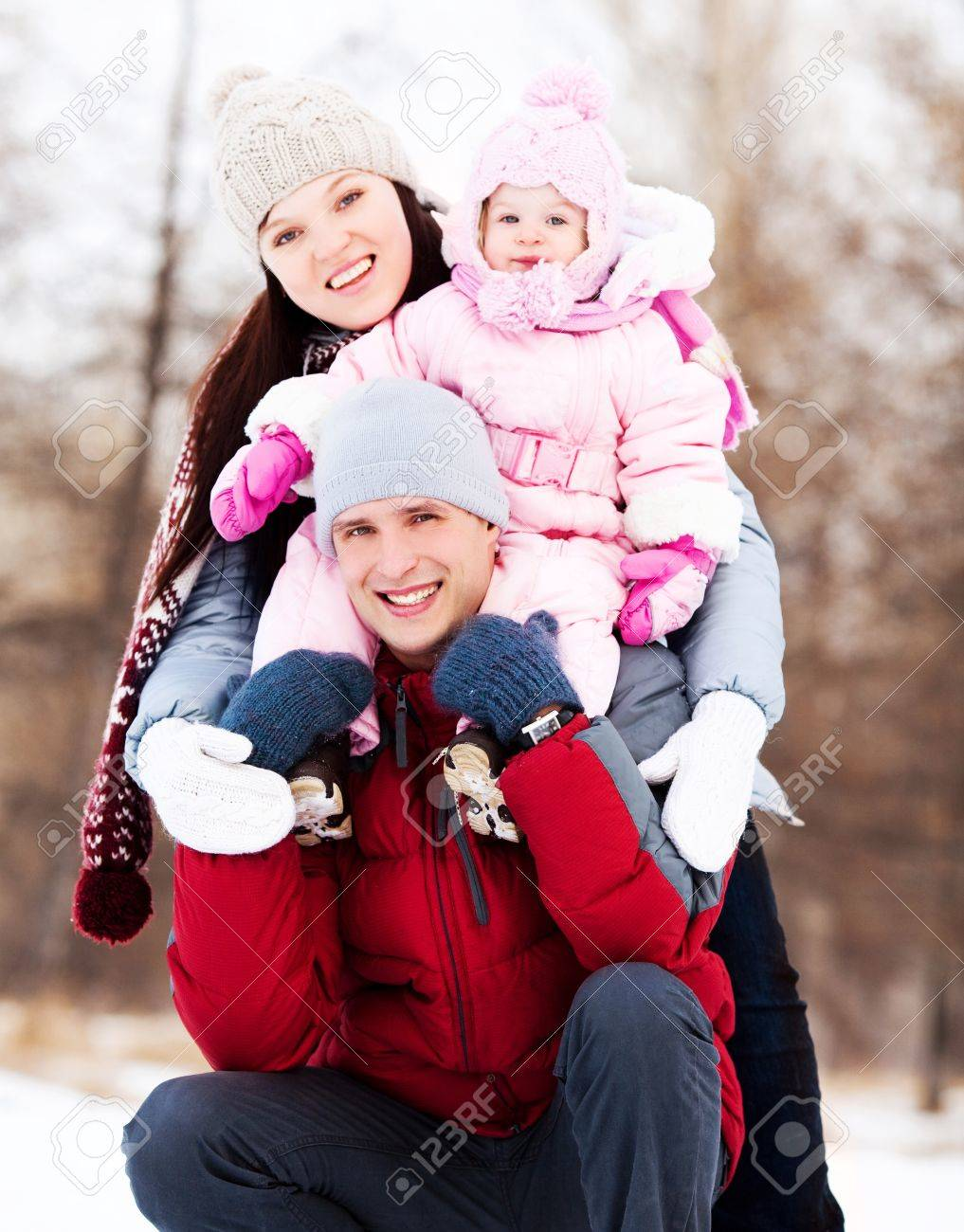happy young father, mother and their daughter spending time outdoor in the winter park (focus on the man) Stock Photo - 11557156
