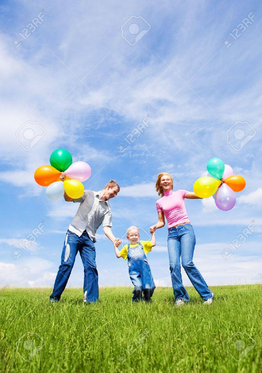 happy family with balloons running outdoor on a warm summer day Stock Photo - 12070702
