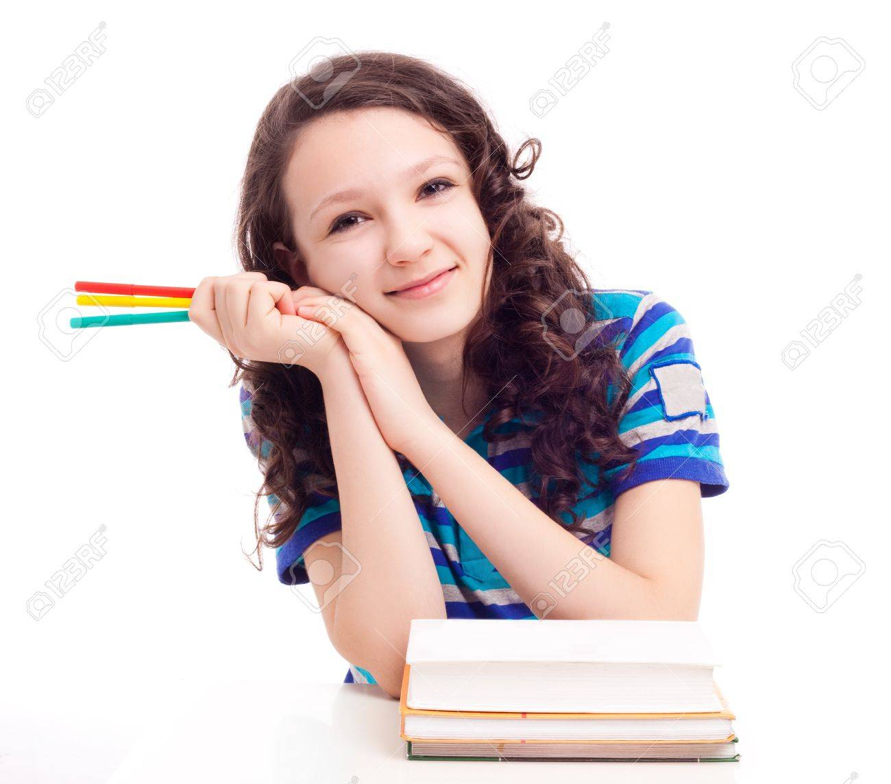 thirteen year old schoolgirl sitting by the table with pens and books, isolated against white background Stock Photo - 12282700