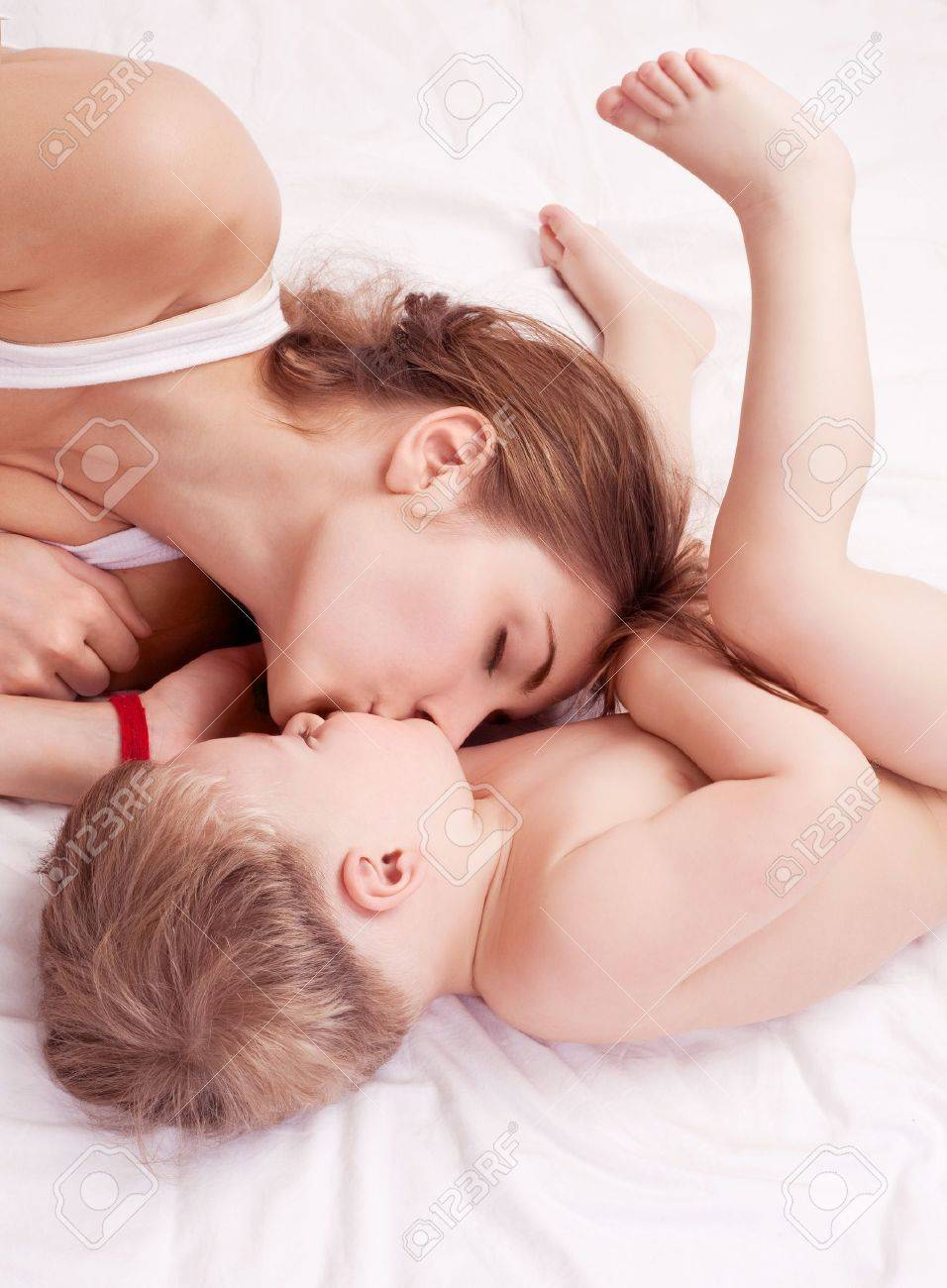 happy young mother and her two year old son embracing and kissing  in bed at home Stock Photo - 12282783