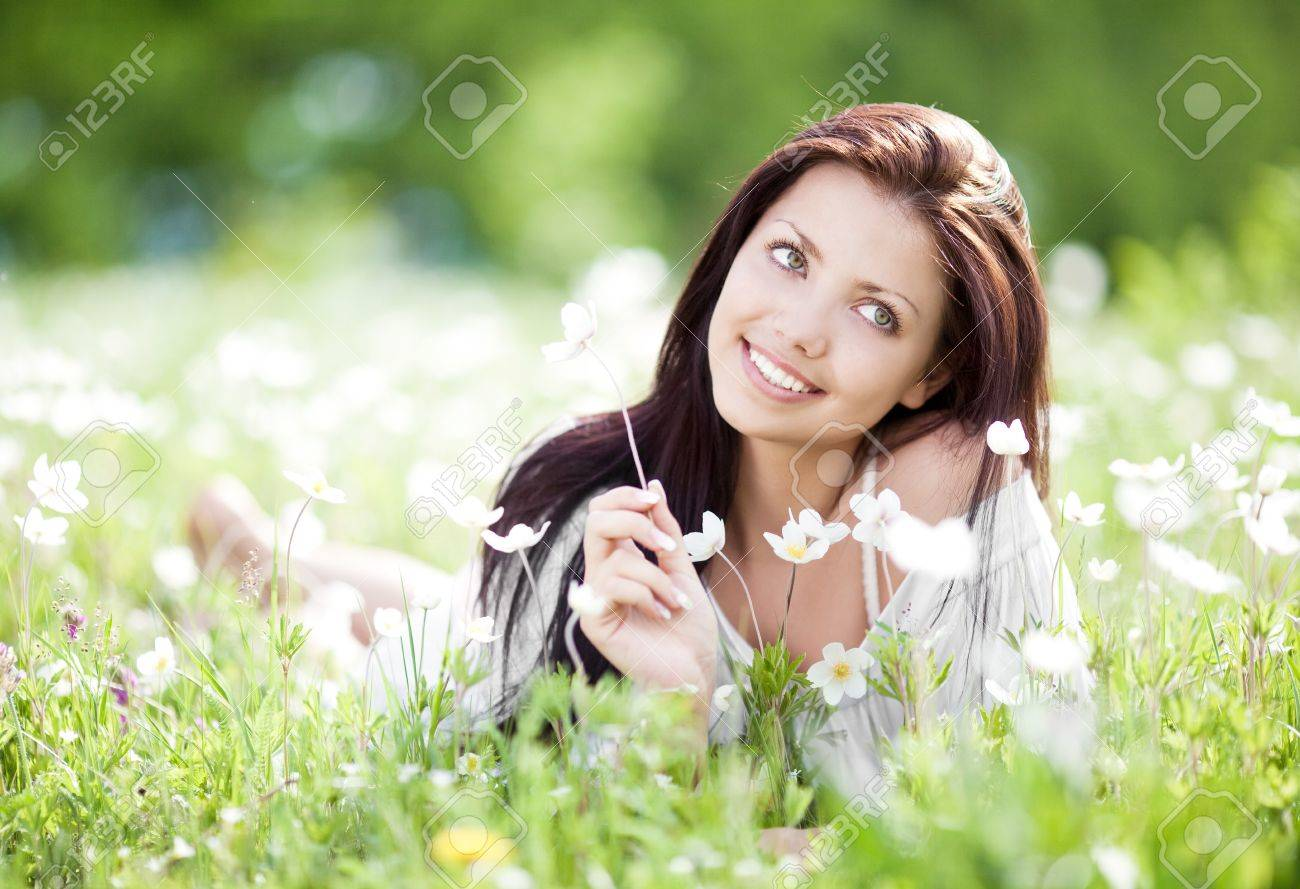 beautiful young brunette woman relaxing on the  meadow with white flowers  on a warm summer day Stock Photo - 13046719