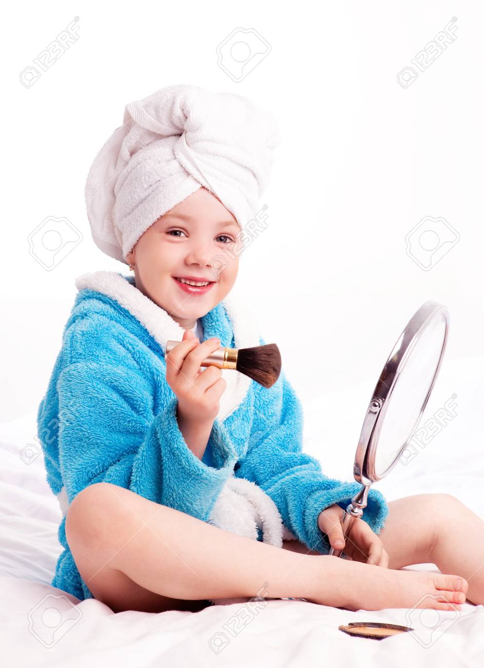 beautiful five year old girl with a mirror applying makeup on her face in bed at home Stock Photo - 13046646