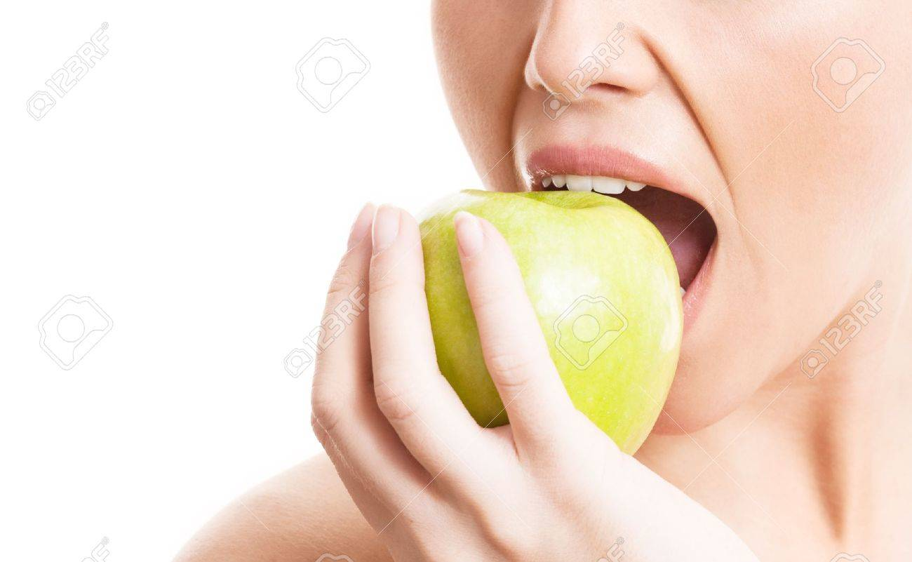 closeup of the face of a woman eating a green apple, isolated against white background, copy space for your text to the left Stock Photo - 13895661