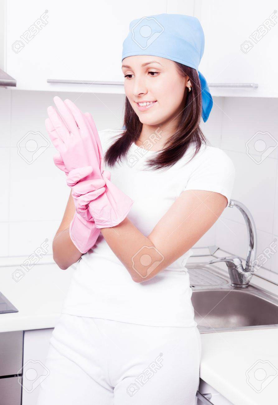 beautiful happy young housewife putting on rubber gloves, in the kitchen at home Stock Photo - 16671917