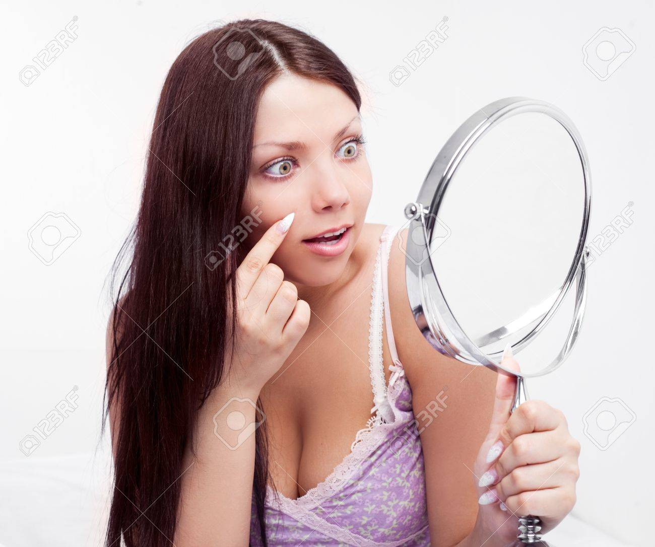 beautiful worried brunette woman having skin problems, with a mirror in bed at home Stock Photo - 16758098