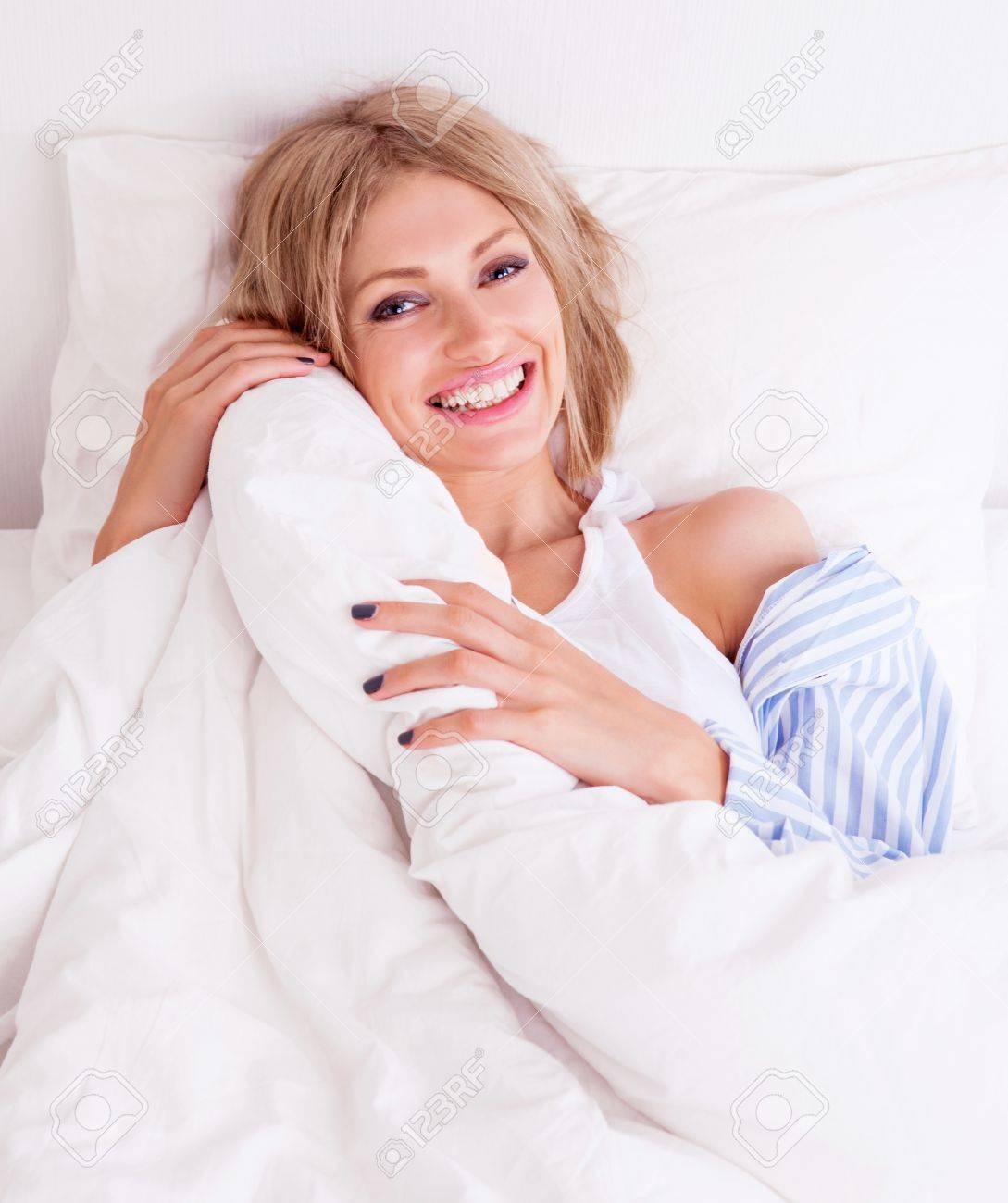 02bcf6ca9c452b beautiful young woman wearing pajamas in bed at home Stock Photo - 21621968