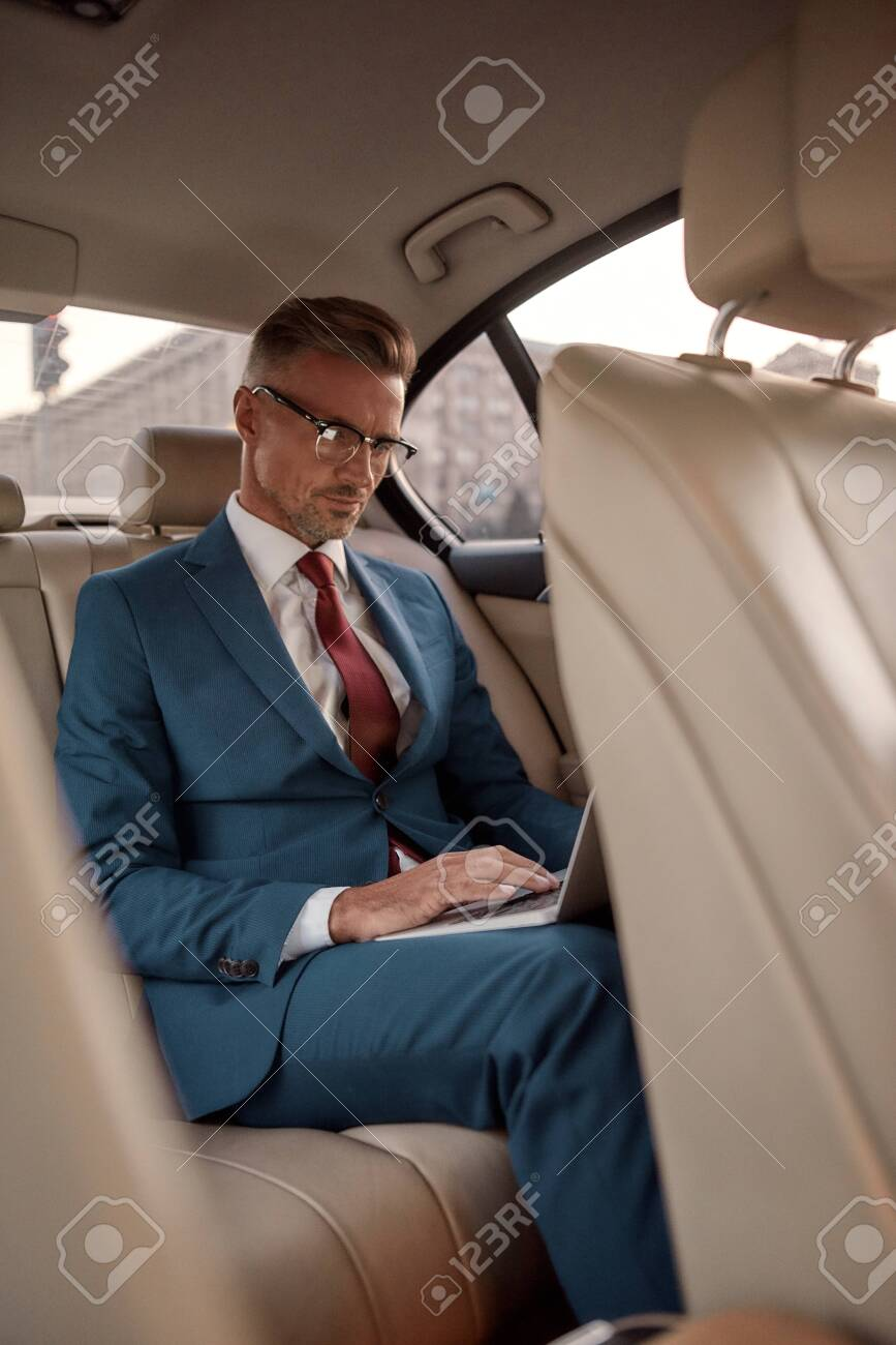 Never stop working. Serious mature businessman in full suit working on his laptop while sitting in the car - 142015969