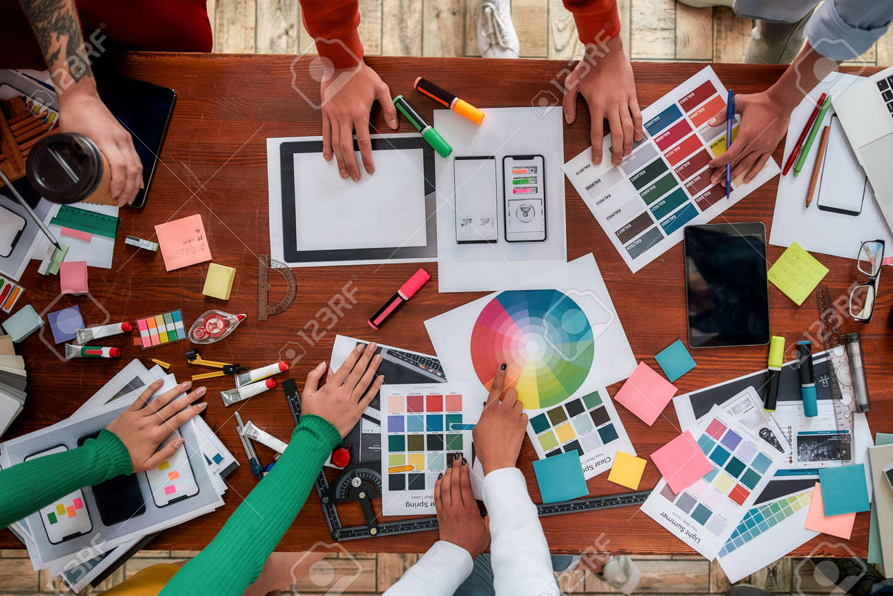 Mobile app design. Top view of designers discussing sketches, choosing colors from palettes lying on the desk while having a meeting in the modern office - 143198919