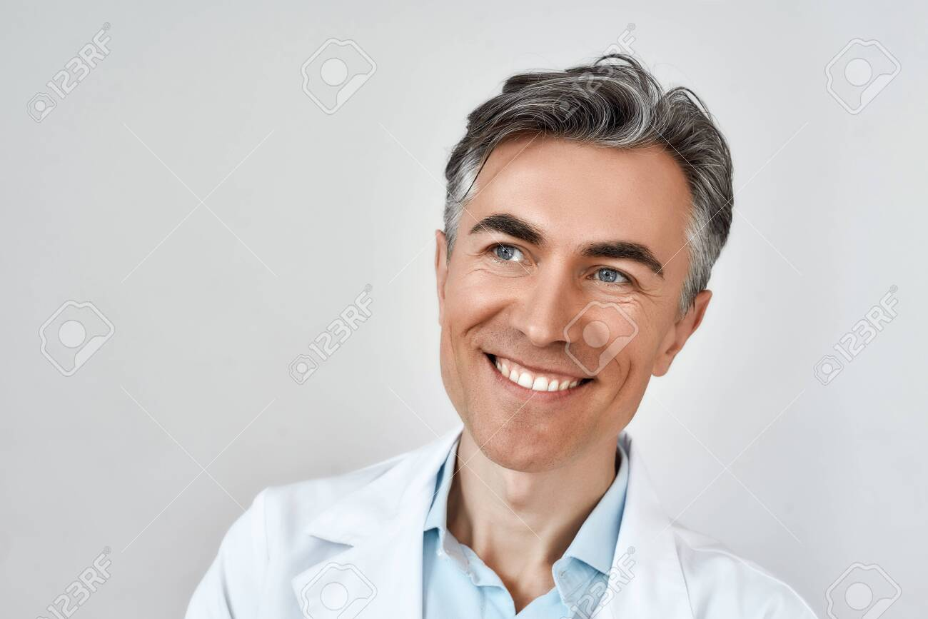 Close up portrait of senior cheerful male doctor smiling while posing against grey background in studio. Headshot - 151504558