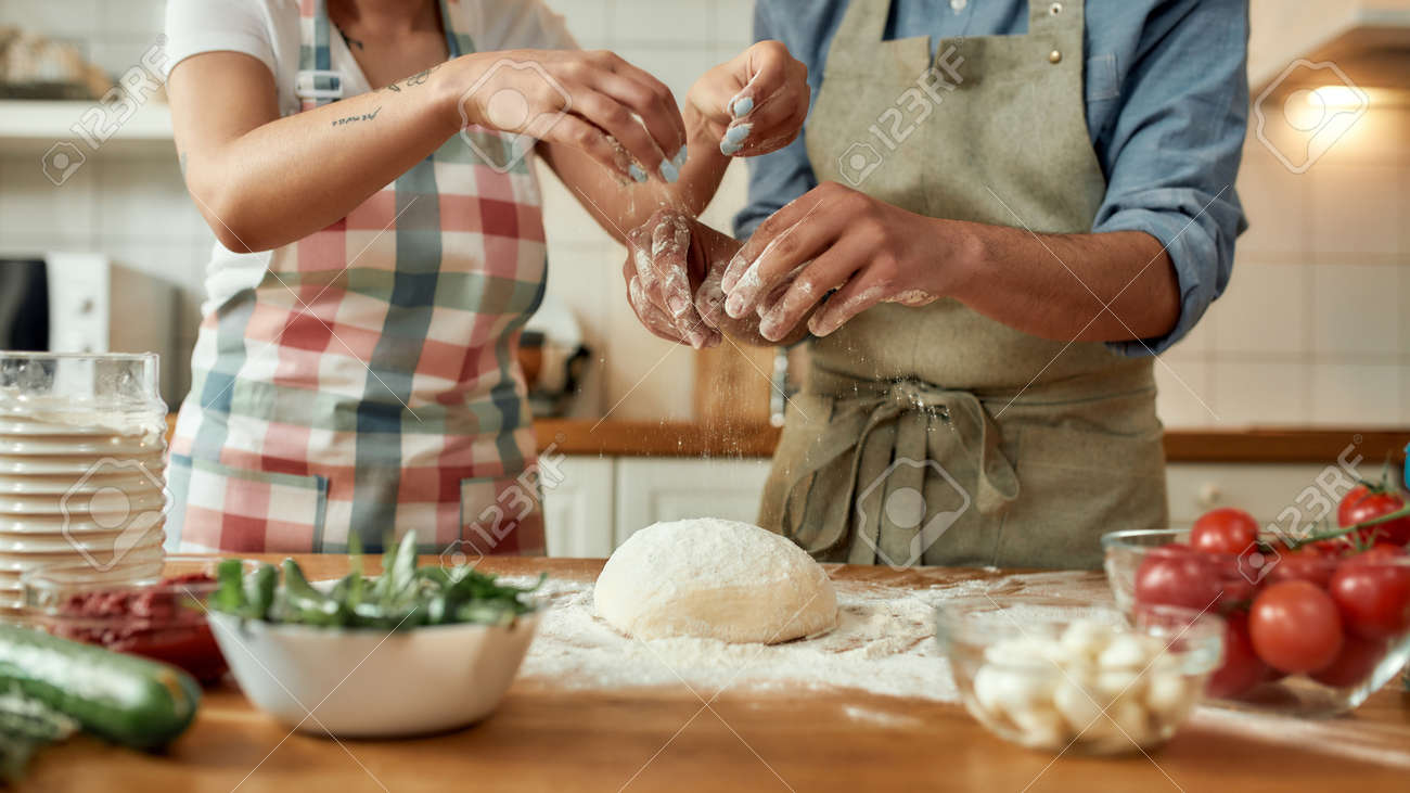 Cropped shot of couple preparing the dough together. Young man and woman in apron cooking, making pizza at home. Hobby, lifestyle - 154453452