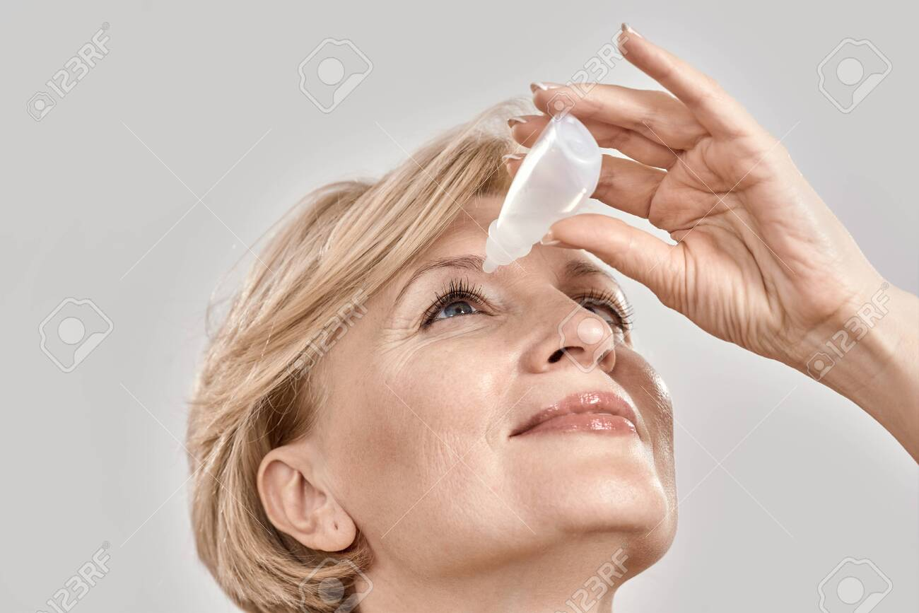 Close up portrait of attractive middle aged woman applying eye drops, standing isolated over grey background - 159098777