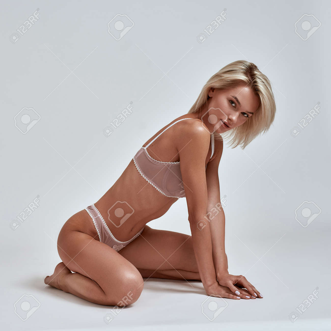 Young sensual woman with perfect slim body wearing lingerie looking playful at camera while posing sitting isolated over grey background - 165041939